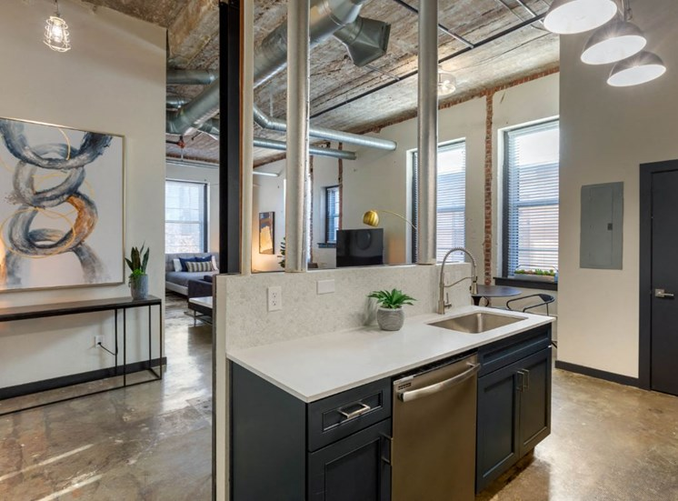 Industrial Style Apartment with Exposed Concrete and Ducts, Kitchen with Breakfast Bar with Stools and Blue Cabinets Under White Counters
