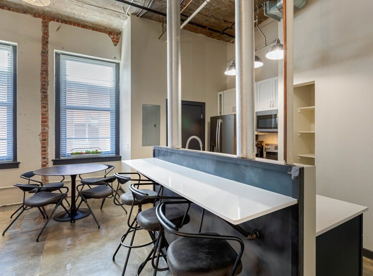 Industrial Style Apartment  with Exposed Ducts and Concrete, Kitchen with Breakfast Bar, White Cabinets, Stainless Steel Appliances and Built In Shelves Next To Dinning Table Under Windows