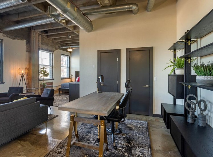 Industrial Style Apartment with Exposed Concrete and Ducts, with Desk, Shelf with Decorations, Couch  and Armchairs Next to Open Bed Area