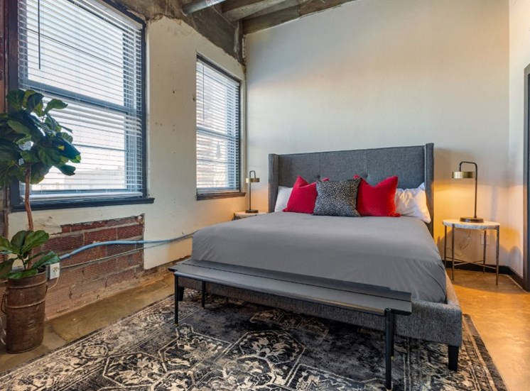 Industrial Style Apartment Bedroom with Windows, Bed, Nightstand and Plants