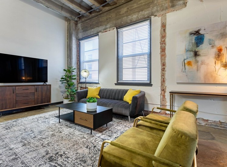Industrial Style Apartment  with Exposed Ducts and Concrete, Area Rug Under Bright Green Armchairs, Coffee Table and Couch under Windows Between Accent Table Under Art and Entertainment Center Under TV