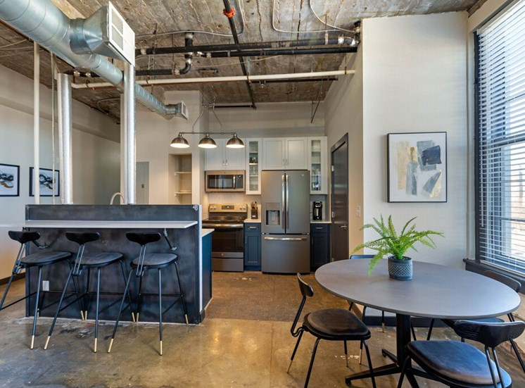 Industrial Style Apartment with Exposed Concrete and Ducts, Kitchen with Breakfast Bar, White Upper Cabinets and Dark Blue Lower Cabinets Around Stainless Steel Appliances and Dinning Room with Dinning Table Next to Window