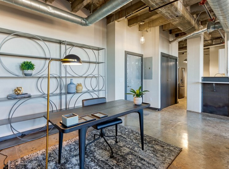 Industrial Style Apartment  with Exposed Ducts and Concrete, Area Rug Under Desk in Front of Contemporary Shelf with Plants and Decorations Next to Kitchen with Breakfast Bar