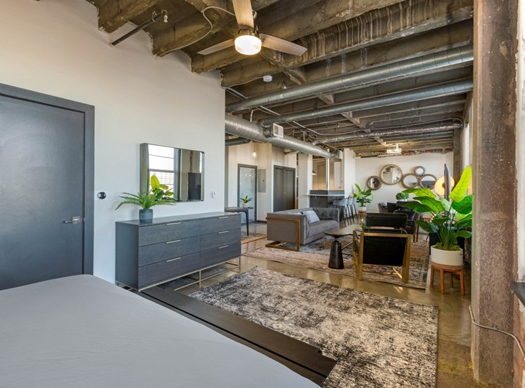 Industrial Style Studio with Exposed Ducts, Dresser, Rugs, Armchairs, Couch, Plants and Breakfast Bar off Kitchen in the Background