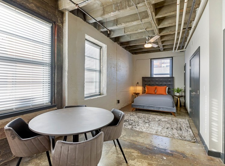 Industrial Studio with Open Bed Area with Bed Next to Dinning Table with Contemporary Table and Chairs Next to Windows