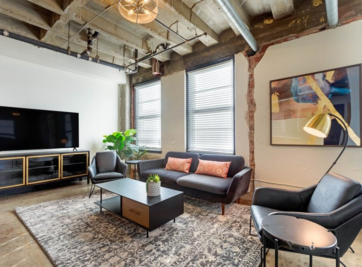 Industrial Style Apartment Living Room with Exposed Ducts and Concrete, Windows, Contemporary Couch, Armchair, Coffee Table, Side Table and Entertainment Center Under TV
