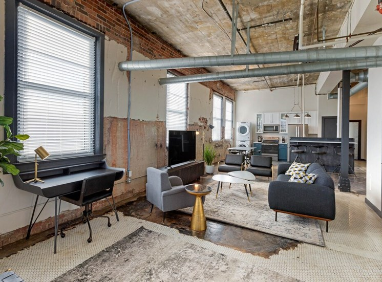 Industria; Apartment with Open Floor Plan, Exposed Ducts and Concrete with Desk, Chairs, Couch TV, TV stand and Kitchen in the Background