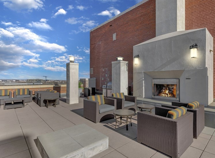 Rooftop Terrace Lounge with Cushioned Patio Armchairs Surrounding Concrete Fireplace Next to Grills with City View in the Background
