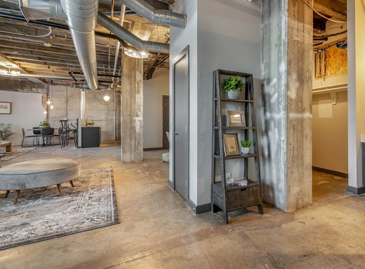 Industrial Style Apartment with Exposed Ducts and Concrete with Decorative Shelves, Area Rug, Ottoman and Dinning Table in the Background