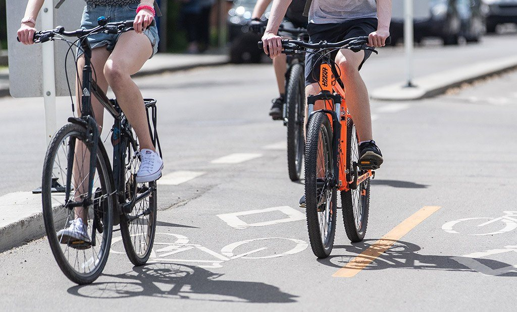 Riding bikes and bicycles on Whyte Avenue Old Strathcona Edmonton Alberta