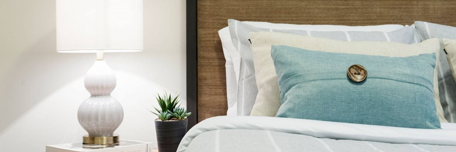 nightstand with lamp beside bed
