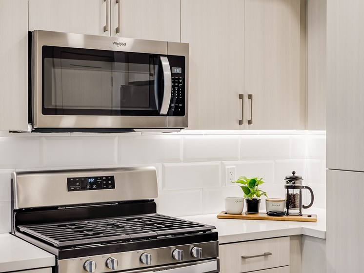 Modern Luxury Kitchen with 5 Burner Gas Range Backsplash Under Cabinet Lighting and Stainless Steel Appliances at The Club at Enclave Apartments in Chula Vista, CA
