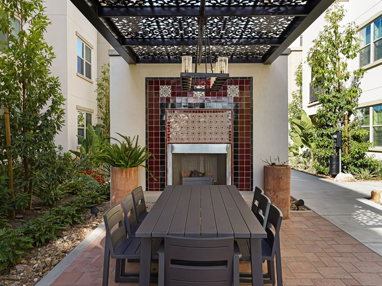 Outdoor Dining Area with Fireplace located in Courtyard at The Club at Enclave Apartments in Chula Vista, CA