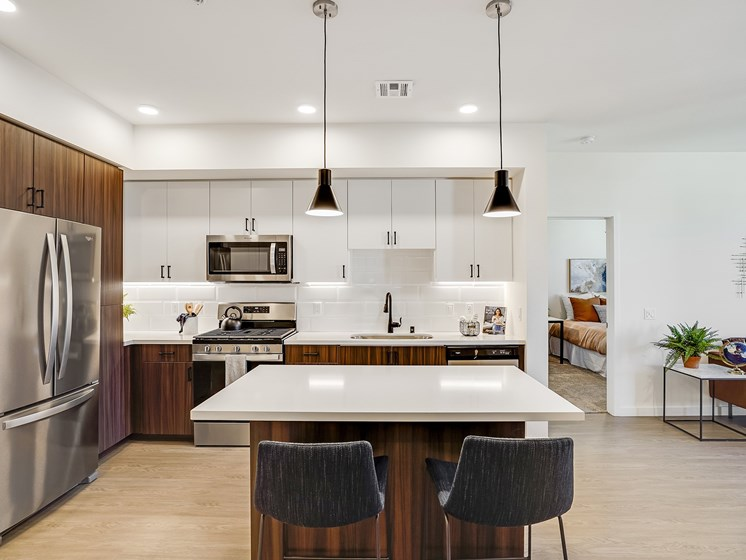 Spacious Penthouse Kitchen Eat In Bar Island French Door Refrigerator Two Tone Cabinetry Black Matte Fixtures White Quartz Counters at The Club at Enclave Apartments in Chula Vista, CA