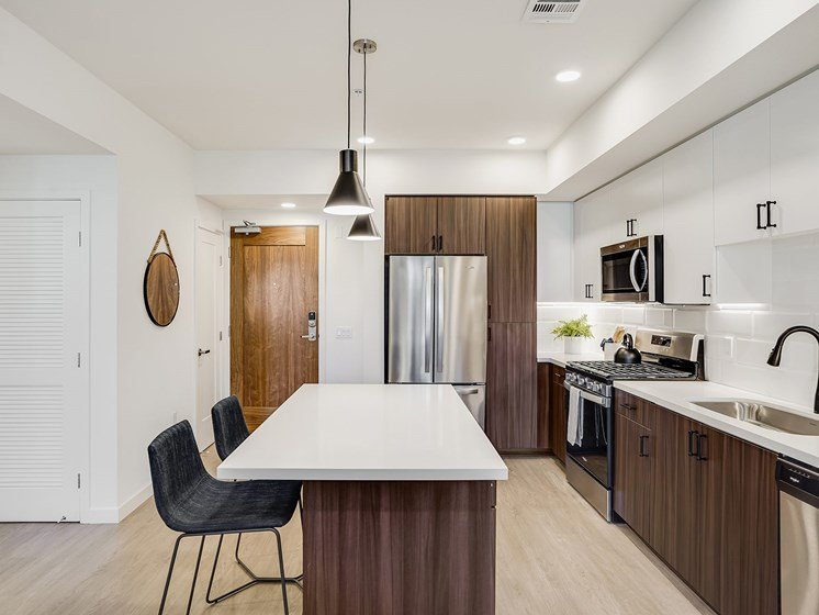 Penthouse Kitchen with Eat In Kitchen Island French Door Stainless Steel Refrigerator Black Matte Fixtures Wood Flooring at The Club at Enclave Apartments in Chula Vista, CA