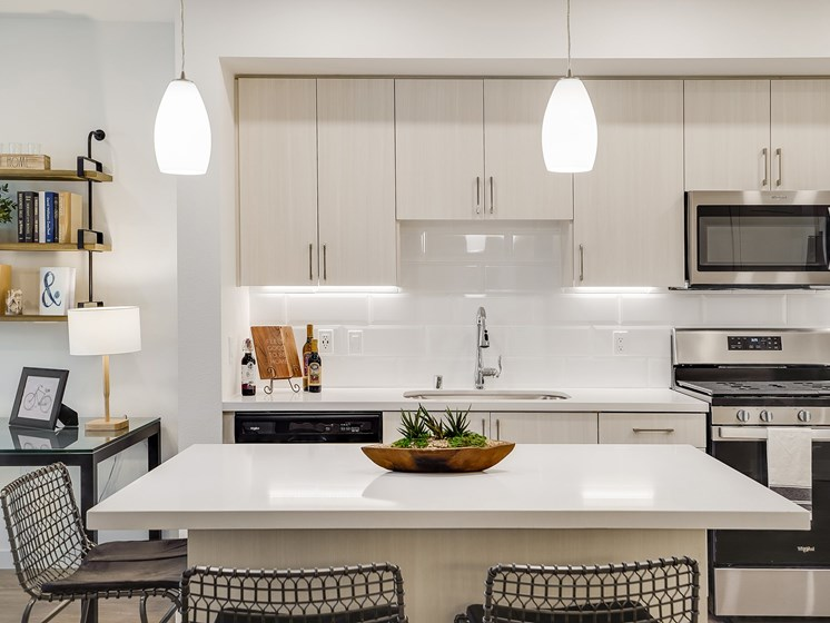 Modern Open Layout Kitchen with Oversized Quartz Island Pendant Lighting White Backsplash Stainless Steel Appliances at The Club at Enclave Apartments in Chula Vista, CA
