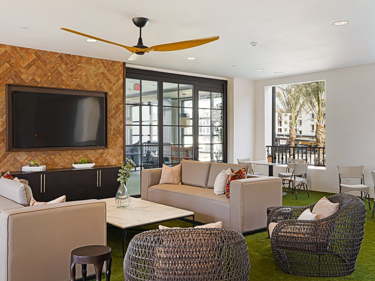 Modern Outdoor Living Room Lounge with TV at The Club at Enclave Apartments in Chula Vista, CA