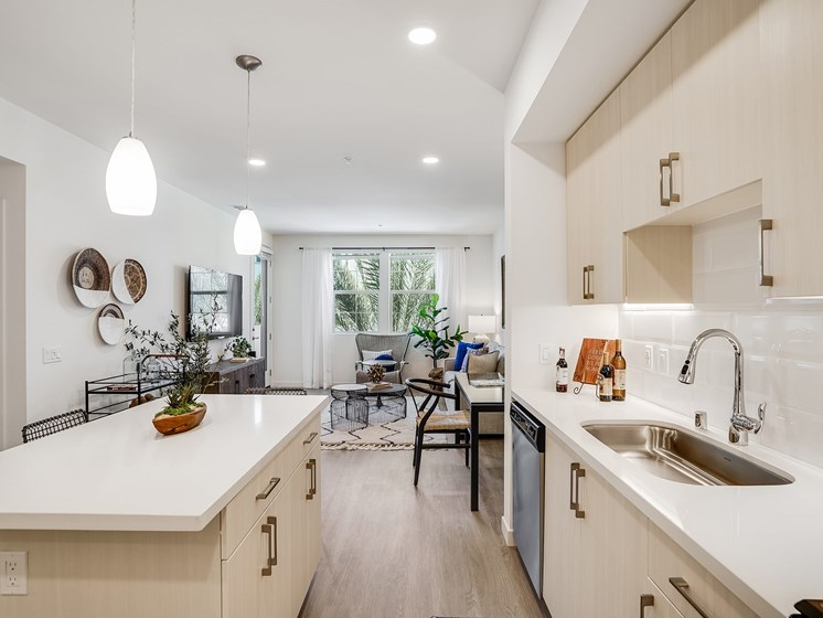 Gorgeous Modern Kitchen with Whit3e Quartz Counters Stainless Steel Appliances Kitchen Island at The Club at Enclave Apartments in Chula Vista, CA