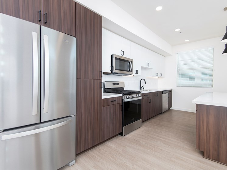 Penthouse Kitchen With White Quartz Countertops At The Club At Enclave Apartments In Chula Vista, CA