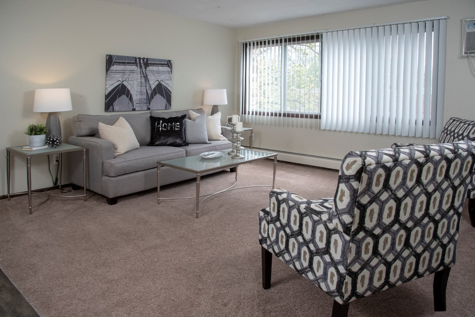 Bright Carpeted Living Room with Large Windows at 600 10th Ave Apartments