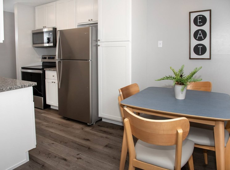 kitchen and dining with new white cabinetry, granite countertops, stainless steel appliances