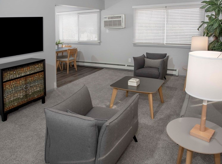 2 bedroom 1 bath living room with chairs, tv and view into dining