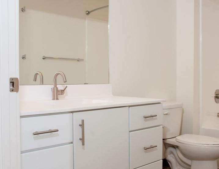Spacious Bathroom with White Cabinetry and Silver Hardware at 700 Central Apartments, Minnesota, 55414