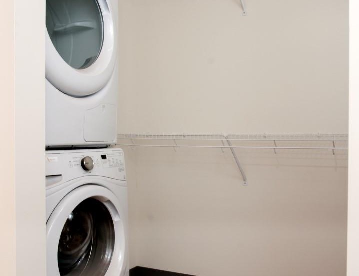 In-Unit Washer and Dryer Machines within Spacious Closet with Built-in Shelving at 700 Central Apartments in Minneapolis, MN