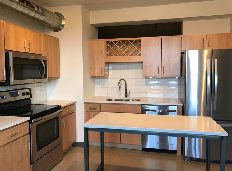 Open Kitchen with Wooden Cabinetry, Stainless Steal Appliances and White Counter Tops at Minneapolis Apartment