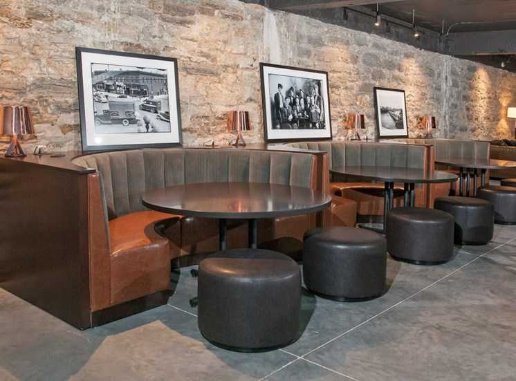 Club Room with Quarter-Circle Booths Around Circle Tables In Front of Exposed Brick Wall at 700 Central Apartments, MN, 55414