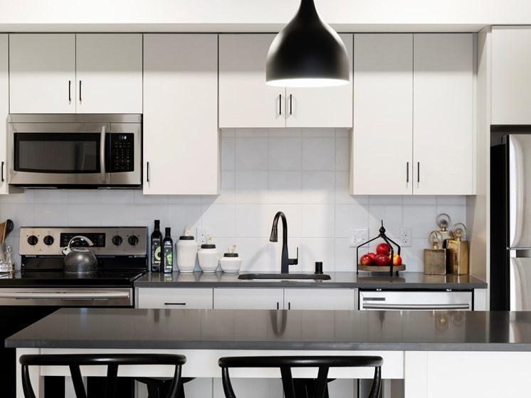 White Cabinetry With Sleek, Silver Appliances at The Hill Apartments in St Paul, MN