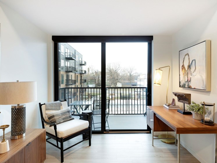 View of Balcony with glass door leading to a cityscape at The Hill Apartments in St Paul, MN