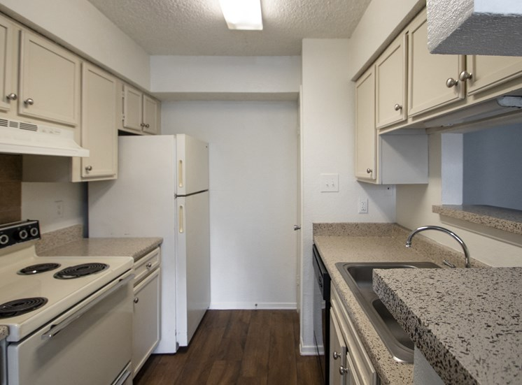 This is a photo of the kitchen in a 1024 square foot 3 bedroom apartment at The Boulders Apartments in Garland, TX.