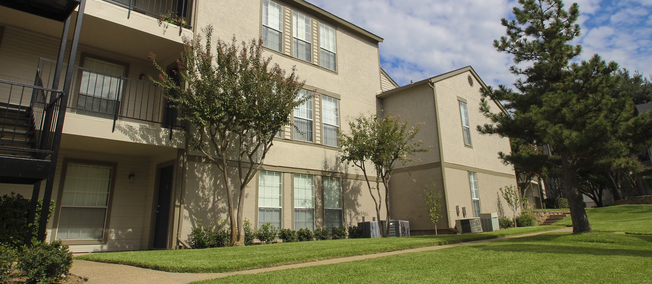 This is a photo of a building exterior/the grounds at The Boulders Apartments in Garland, TX.