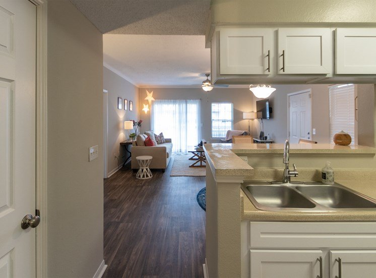 This is a photo of the living room from the kitchen in the 1135 square foot 2 bedroom Retreat floor plan at The Sanctuary at Fishers Apartments in Fishers, IN.
