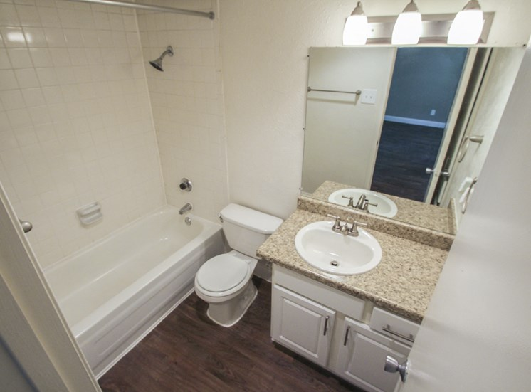 This is a photo of the bathroom with hardwood vinyl flooring in the 751 square foot 1 bedroom apartment at Woodbridge Apartments in Dallas, TX.