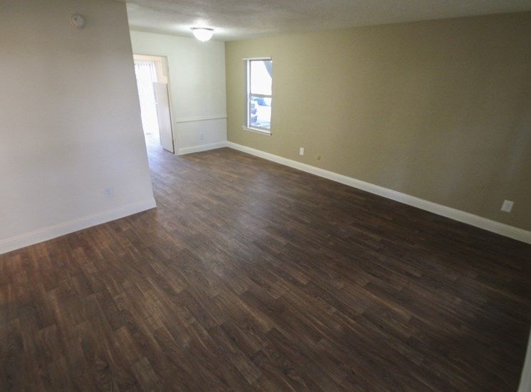 This is a photo of the living room with hardwood vinyl flooring in the 751 square foot 1 bedroom apartment at Woodbridge Apartments in Dallas, TX.