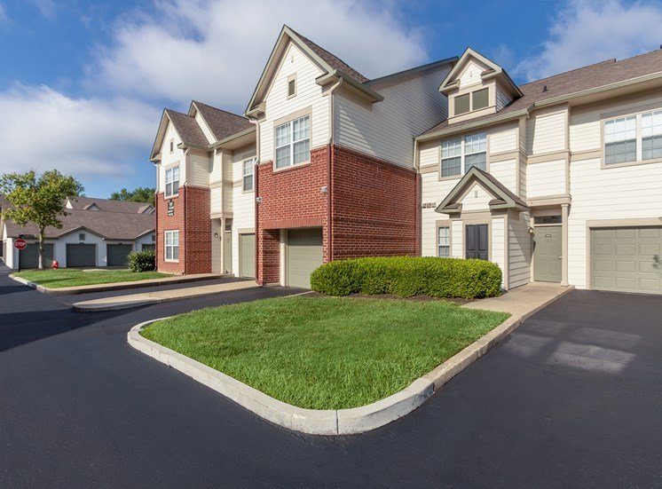This is a photo of apartment exteriors showing private entrances, attached garages and covered parking at The Sanctuary at Fishers in Fishers, IN.