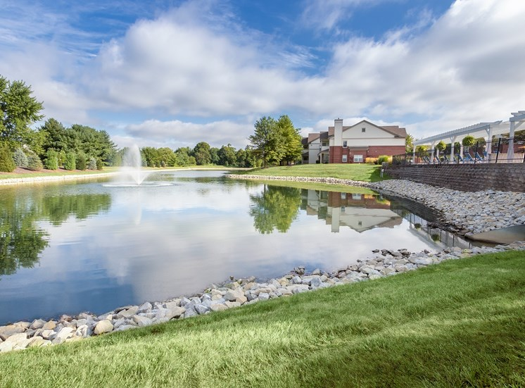 This is a photo of the a pond and fountain with apartment exteriors and the pool deck at The Sanctuary at Fishers in Fishers, IN.