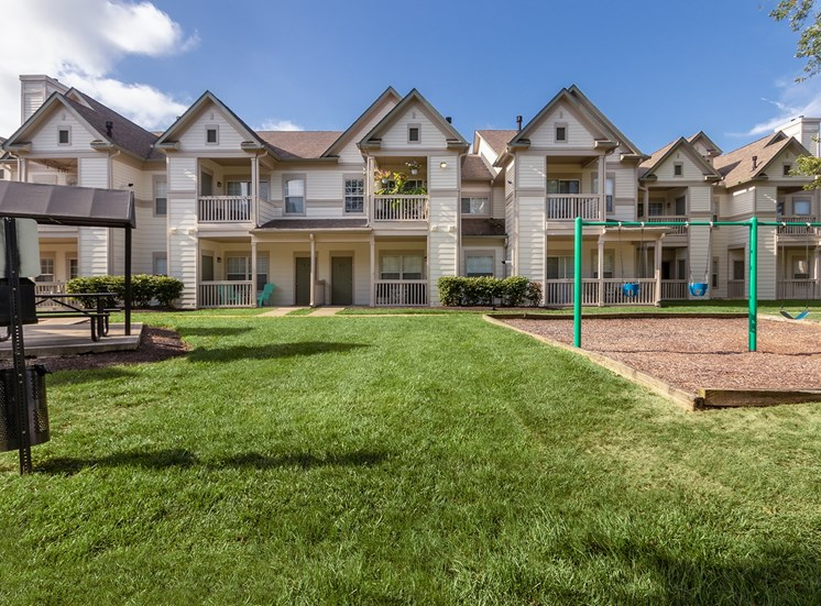 This is a photo of a BBQ grilling station and some swings with apartment exteriors in the background at The Sanctuary at Fishers in Fishers, IN.