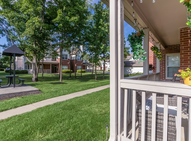 This is a photo of a private patio with a courtyard in the background at The Sanctuary at Fishers in Fishers, IN.