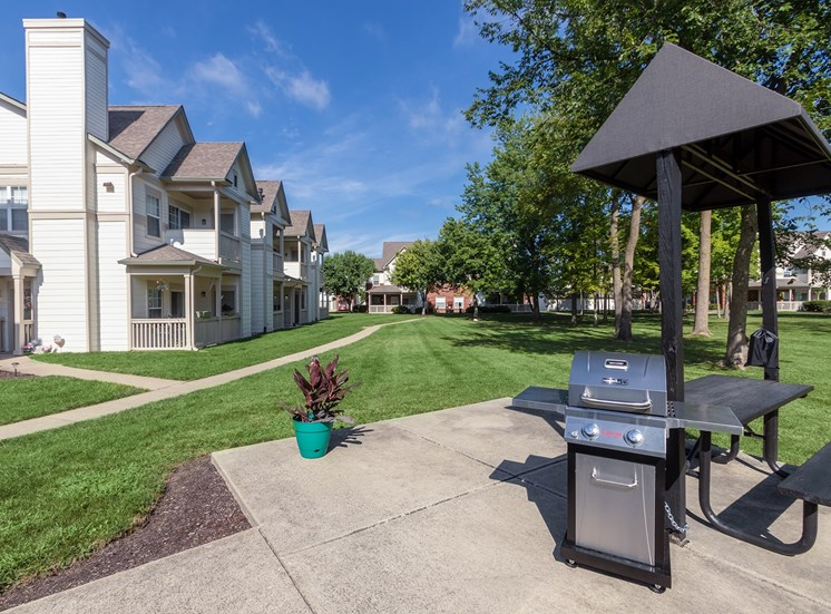 This is a photo of a BBQ grilling station and apartment exteriors at The Sanctuary at Fishers in Fishers, IN.