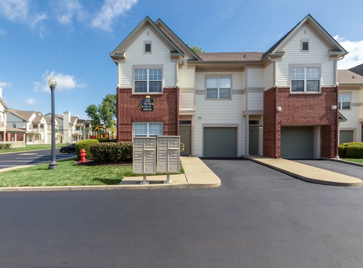 This is a photo of apartment exteriors showing private entrances and attached garages at The Sanctuary at Fishers in Fishers, IN.