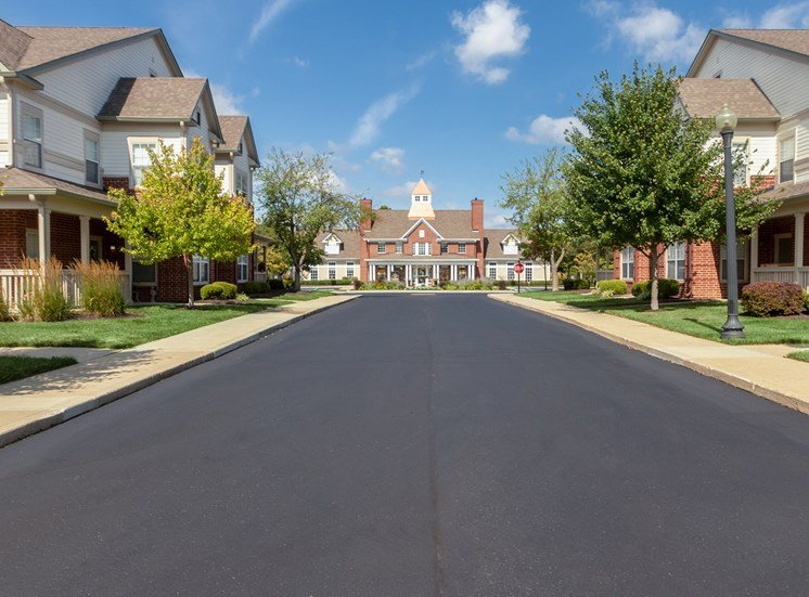 This is a photo of apartment exteriors from the road leading up to the Leasing Office at The Sanctuary at Fishers in Fishers, IN.