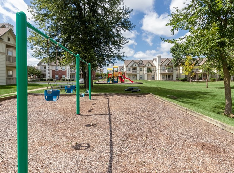 This is a photo of some swings looking towards the playground at The Sanctuary at Fishers in Fishers, IN.