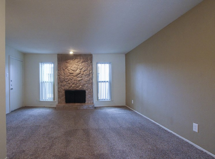This is a photo of the living room with fireplace of the 751 square foot 1 bedroom apartment at Woodbridge Apartments in Dallas, TX.
