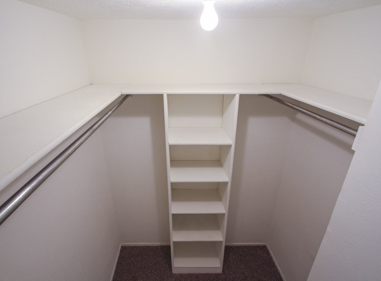 This is a photo of the one of the two walk-in closets in the bedroom of the 751 square foot 1 bedroom apartment at Woodbridge Apartments in Dallas, TX.