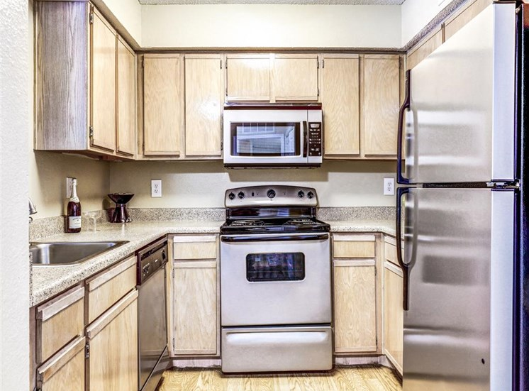 Stainless Steel microwave, dishwasher and refrigerator at Trinity Square Apartments For Rent in North Dallas, TX.