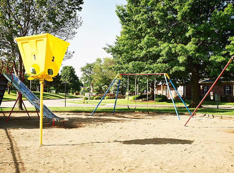 Playground with slides, swings, and basketball hoop at Briarwood Lafayette.