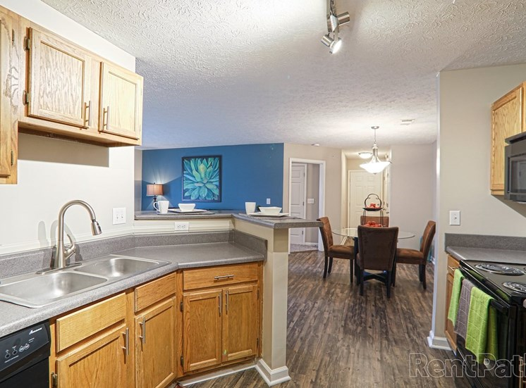 kitchen with stainless steel sink, built-in microwave, and hardwood-style floors at The Point at Fairview Apartments, Prattville, AL, 36066